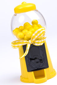 pic of gumball machine  - A yellow toy gumball machine with yellow gumballs and a yellow and white checked bow on a white background - JPG