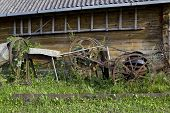 pic of horse plowing  - Retro old rusty farm tools of the early twentieth century rot near wooden house - JPG