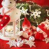 stock photo of home is where your heart is  - Cute couple of little adorable snowmen is standing near the white fairy lantern with a toy heart on it and decorated fir tree branch behind it - JPG