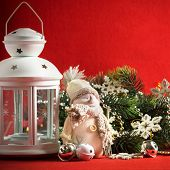 picture of home is where your heart is  - Cute little adorable snowman is standing near the white fairy lantern and decorated fir tree branch behind it - JPG