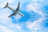 stock photo of wispy  - White jet airplane fly in blue bright wispy cloudy blue sky - JPG