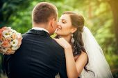stock photo of bridal veil  - Wedding shot of bride and groom in park - JPG