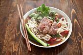 stock photo of rice noodles  - bowl of vietnamese pho in natural light - JPG