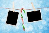 stock photo of candy cane border  - Blank photos and candy cane hanging on clothesline over blue christmas background - JPG