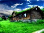 stock photo of unnatural  - colorful old house with grass roof and brilliant colors - JPG