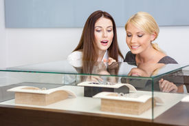 stock photo of jewel-case  - Two women looking at showcase with jewelry at jeweler - JPG