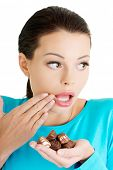 stock photo of embarrassing  - Embarrassment beautiful woman with hand full of chocolates  - JPG