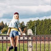 image of climbing rose  - Blond girl in short shorts and denim coat with roses wreath on head turns back having climbed fence with skateboard hung on it