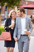 foto of takeaway  - Business Couple Walking Through Park With Takeaway Coffee - JPG