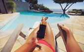 stock photo of pov  - Tanned woman using smart phone by the poolside - JPG