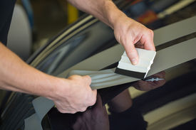 image of bubble sheet  - Car wrapper straightening wrapping foil with a squeegee to remove air bubbles  - JPG