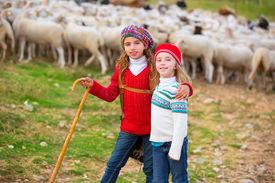 image of shepherdess  - Kid girl shepherdess sisters happy with flock of sheep and wooden stick in Spain - JPG