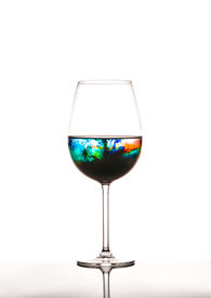 stock photo of polution  - Glass with multicolored water on white background concept of polution - JPG