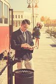 picture of she-male  - Beautiful vintage style couple outside retro train coach have a romantic encounter while he reading book and she race toward him smiling fashion vintage style - JPG