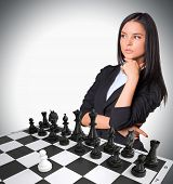 picture of chessboard  - Lost in thought businesswoman with Chessboard and chess pieces - JPG
