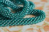 stock photo of aquamarine  - Beads of color the aquamarine connected in the form of a plait - JPG