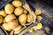 stock photo of crate  - Raw Organic Golden Potatoes in the Wooden Crate on Aged Wood Planks Table - JPG
