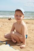 foto of azov  - Boy sitting at the seaside on the sand - JPG