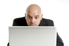 picture of spanish money  - young businessman typing on computer keyboard with funny face expression on watching internet porn online or making money gambling on line isolated on white background - JPG