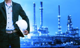 stock photo of refinery  - engineering man and safety helmet standing against oil refinery plant in heavy petrochemical industry estate - JPG
