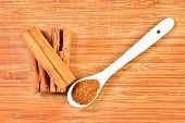 picture of cinnamon  - macro photograph of cinnamon sticks dry beside a teaspoon of ground cinnamon - JPG
