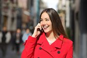 stock photo of people talking phone  - Cheerful woman talking on the phone in the street wearing a red jacket - JPG