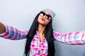 picture of funky  - Happy young African woman in funky clothes making selfie while standing against grey background - JPG