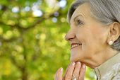 stock photo of beautiful senior woman  - Portrait of beautiful senior woman in autumn park - JPG