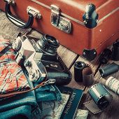 pic of old suitcase  - Old travel suitcase sneakers clothing map filmstrip and retro film camera on wooden background - JPG