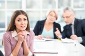stock photo of interview  - Young woman having an interview or business meeting with employers. Woman really wanting to get the job. Office interior with big window