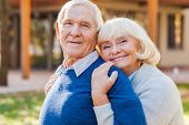 stock photo of bonding  - Happy senior couple bonding to each other and smiling while standing outdoors and in front of their house - JPG