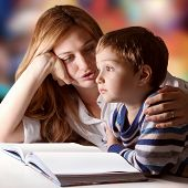 stock photo of bible story  - Little boy listening to his mother telling him stories - JPG