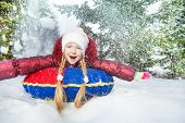 picture of inflatable slide  - Excited girl on snow tube in winter during day in the fir tree forest - JPG
