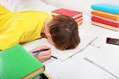 stock photo of fatigue  - Sad and Tired Teenager doing Homework at the Home - JPG