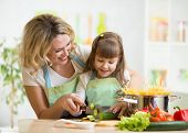 picture of apron  - Cute mother teaches kid child cooking on kitchen - JPG