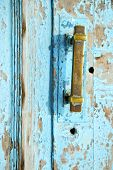 pic of nail paint  - metal nail dirty stripped paint in the brown red wood door and rusty knocker - JPG