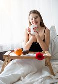 foto of bed breakfast  - Young woman in lingerie lying in bed and having breakfast - JPG