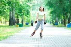 stock photo of inline skating  - Roller skating sporty girl in park rollerblading on inline skates - JPG