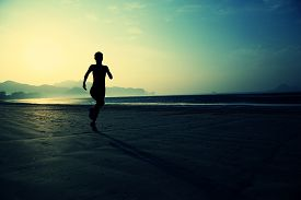 image of morning sunrise  - young healthy lifestyle woman running at sunrise beach - JPG