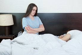stock photo of disappointed  - Dissatisfied beautiful young woman in bed with sad and disappointed expression on her face sex problems in long relationship marriage while man sleeping - JPG