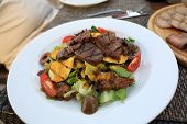 picture of veal  - Salad with grilled veal and mushrooms on the white plate - JPG