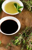 stock photo of vinegar  - Olive oil balsamic vinegar and herbs on vintage wood background from above - JPG