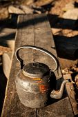 picture of kettles  - Old kettle in wooden bench outdoors in sunlight - JPG