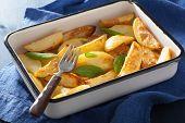 stock photo of baked potato  - baked potato wedges in enamel baking dish - JPG