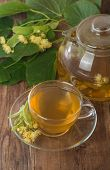 picture of teapot  - teapot and cup with linden tea and flowers on wooden table - JPG
