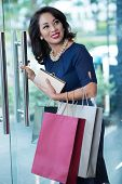 pic of clutch  - Glamorous Vietnamese woman with clutch and shopping bags leaving the store - JPG
