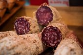 stock photo of charcuterie  - pile of salami cut in a half sold on market - JPG
