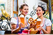 picture of pretzels  - Girlfriends with Pretzel and Beer in Bavarian Inn eating and drinking - JPG