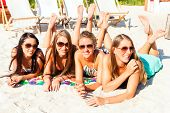 stock photo of sun-tanned  - Four woman lying on beach sand - JPG