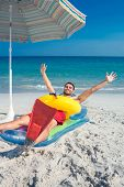 picture of flipper  - Man lying on the beach with flippers and rubber ring on a sunny day - JPG